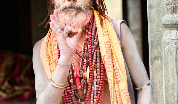 KATHMANDU, NEPAL - MAY 04: Holy Sadhu man with beard and traditional face paint sitting in Pashupatinath Temple on May 04, 2014 in Nepal, Kathmandu.